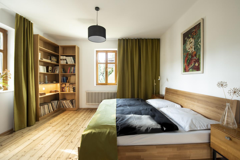 K výrazné proměně ložnice přispěly barvy, jejichž výběr nasměroval obraz ze skleněné drti nad postelí. Závěsy podšité další látkou působí luxusním dojmem. Část nové knihovny z masivu podsvítily LED pásky.