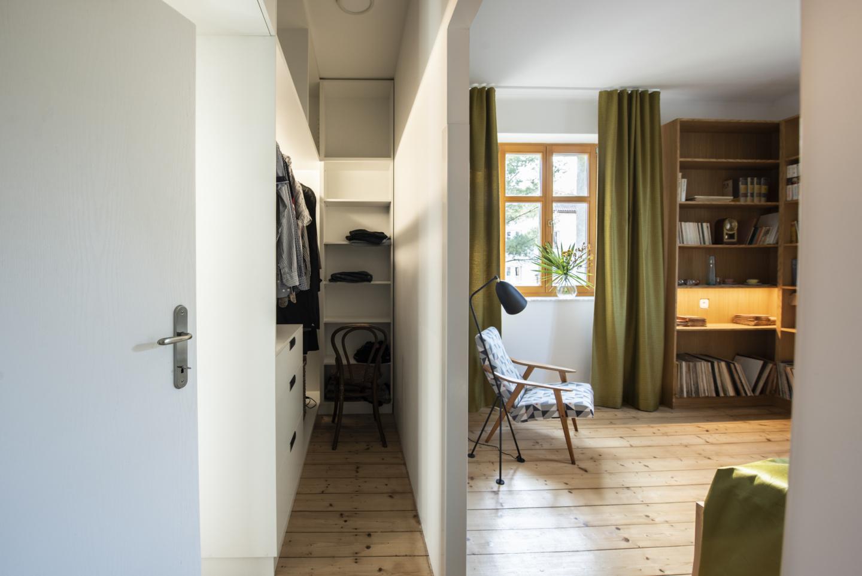 Nová průchozí šatna je úzká, ale má oddělené úložné prostory pro dvě osoby. Designérka ji oddělila od ložnice příčkou.