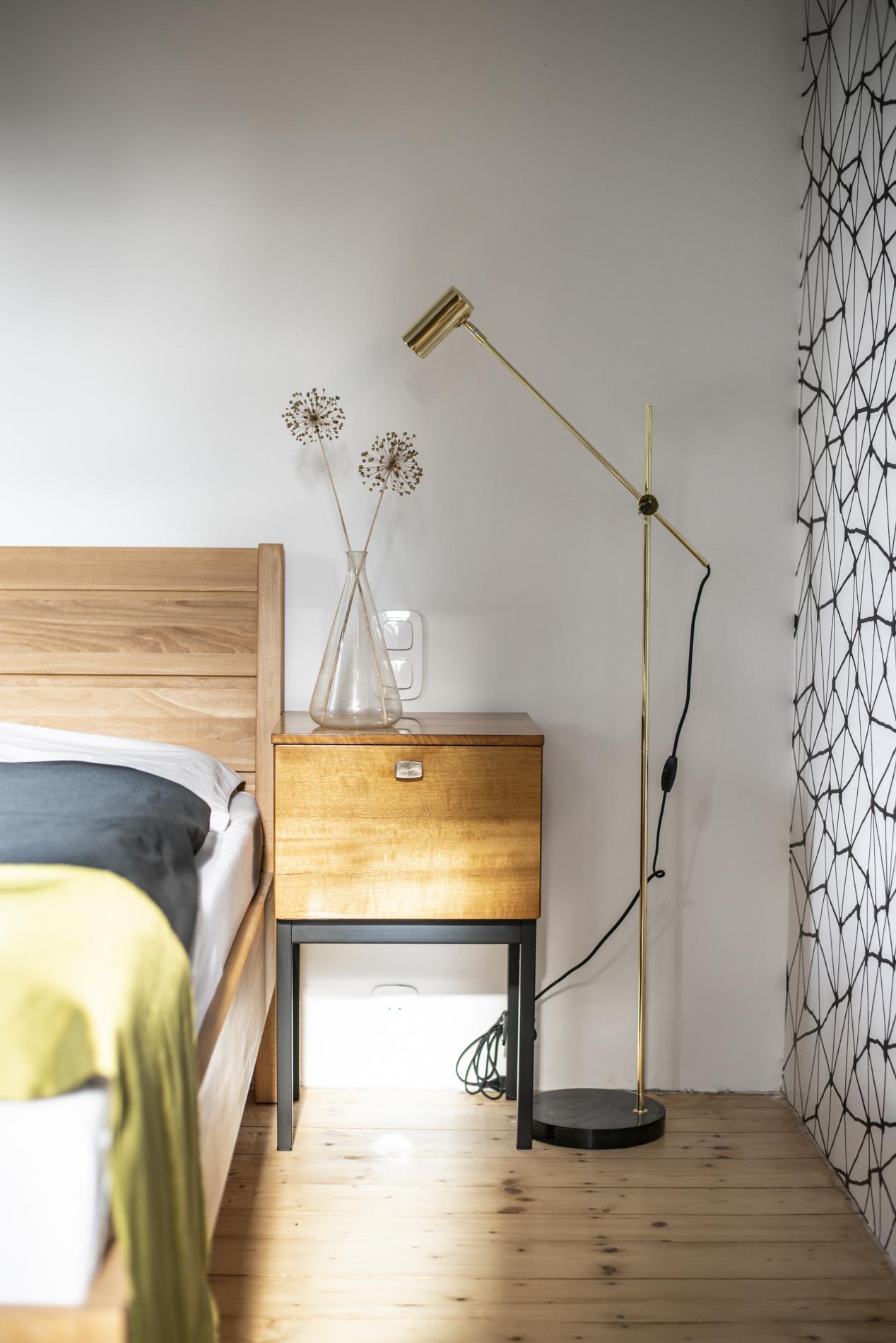 Postel i smrková podlaha zůstaly z předchozího stavu. Místo lampiček u nočních stolků jsou použité podlahové lampy, mosazné a do páru.